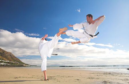 Young adult men practicing Karate on the beach. One is in a high kick and the other flying through the air (some movement on the edges) photo