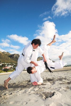 throwing: Young adult men with black belt practicing fighting on the beach on a sunny day – movement on extremities
