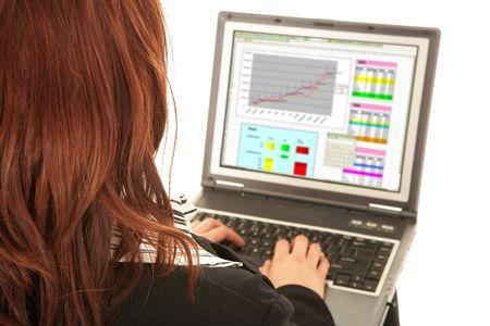 hoja de calculo: Redheaded de negocios que trabajan en ordenador port�til. Ver m�s de su hombro con un fondo blanco. Enfoque en el hombro, pantalla borrosa  Foto de archivo