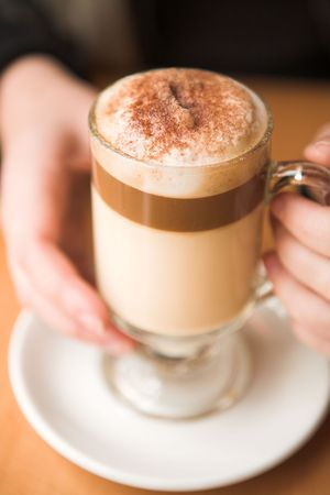 Cafe Latte held by a young woman on a table. Shallow Depth of Field � Foam in focus