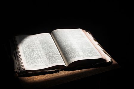 Old open bible lying on a wooden table in a beam of sunlight (not an isolated image) Shallow Depth of field � Focus on middle text Stock Photo - 1356126