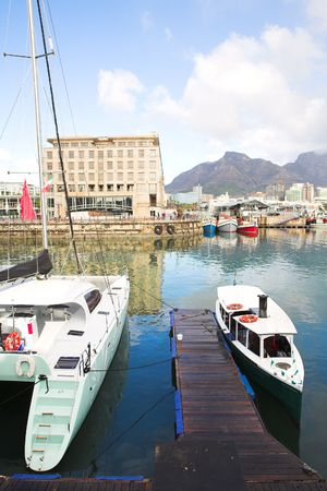 Two tourist boats in the Cape Town waterfront harbor with three boats reflecting in the water in the background and part of the city skyline visible photo