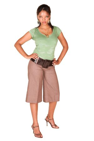 short sleeved: A short smiling African businesswoman with brown trousers and a short sleeved green top and a faux leather belt. She has one arm in her side and is smiling at the viewer. Isolated on white. Stock Photo