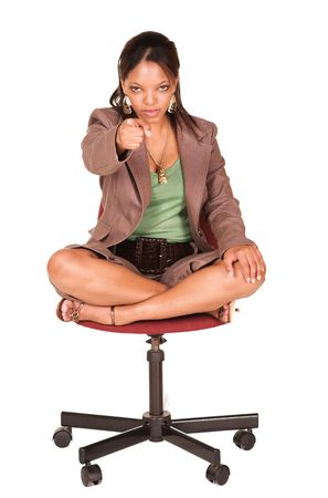 short sleeved: A short smiling African businesswoman with brown trousers and a short sleeved green top and a faux leather belt. She is sitting on an office chair, and serious. She is pointing at the viewer (focus on face) Stock Photo
