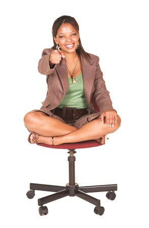 short sleeved: A short smiling African businesswoman with brown trousers and a short sleeved green top and a faux leather belt. She is sitting on an office chair, and smiling. She is pointing at the viewer (focus on face) Stock Photo