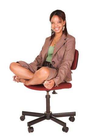 short sleeved: A short smiling African businesswoman with brown trousers and a short sleeved green top and a faux leather belt. She is sitting on an office chair, and smiling.  Stock Photo