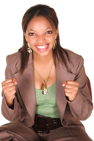 A short smiling African businesswoman with brown trousers and a short sleeved green top and a faux leather belt. She has fist in the air, success photo