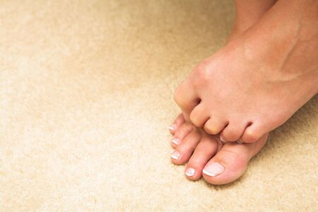 Feet and toes of a young adult woman. She is hiding her toes and curling them up. Stock Photo