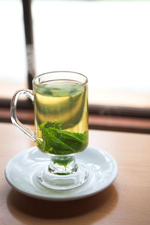 field mint: Hot green mint tea standing next to a window with whole mint leaves (shallow Depth of Field)