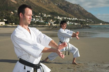 kata: Young adult men with black belt practicing a Kata on the beach on a sunny day Stock Photo