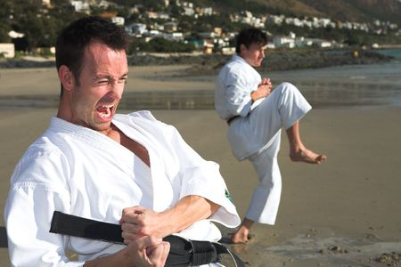 Young adult men with black belt practicing a Kata on the beach on a sunny day Stock Photo