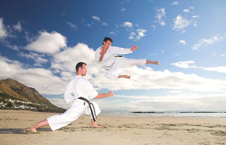 Young adult men with black belt practicing on the beach on a sunny day. The man doing the flying kick in the background has movement. Focus on the standing man photo