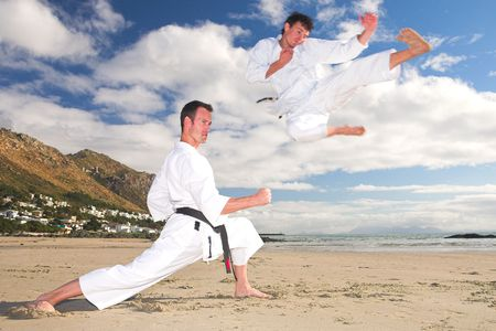 Young adult men with black belt practicing on the beach on a sunny day. The man doing the flying kick in the background has movement. Focus on the standing man Stock Photo - 1356107