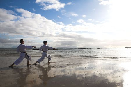 Young adult men with black belt practicing a Kata on the beach on a sunny day. Sunspots and flare from direct sunlight visible