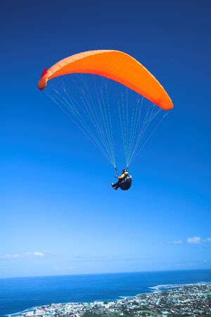 Paraglider launching from the ridge with an orange canopy against a blue sky. The town of Hermanus (Western Cape, South Africa) in the bottom of the image  Stock Photo
