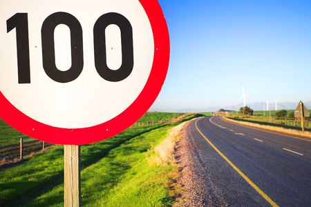 saturated: Warning sign or road sign for the maximum speed limit next to an empty road on a sunny summer day. Focus on the numbers � saturated colors (polarized image) Stock Photo