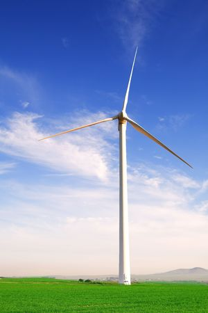 electricity generator: Wind powered electricity generator standing against the blue sky in a green field on the wind farm.  Stock Photo