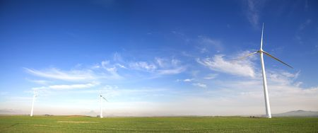 Panoramic image of wind powered electricity generator standing against the blue sky on a wind farm  Stock Photo