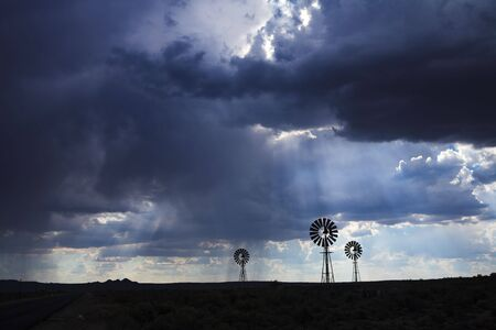 Brewing thunderstorm in the dessert area of the Karoo in South Africa. Three wind pumps silhouetted against the skyline with sunbeams shining through the clouds.