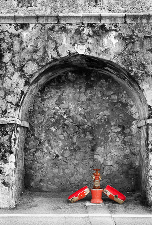 Fire Hydrant in the old Harbour blocking wall at Baie Des Anges in Antibes, France.  Black and White with selective colour, Copy space.   photo
