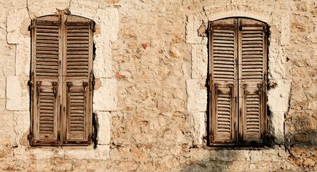 Window shutters of an old building in Antibes, France. Sepia tone.   Copy space.   Stock Photo