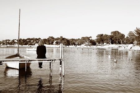 A person sitting on a pier in Antibes, France.  Sepia tone.  Copy space. photo