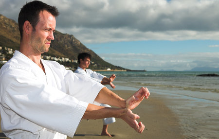 Young adult men with black belt practicing a Kata on the beach on a sunny day photo