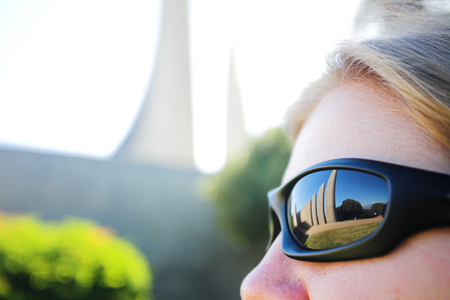 Famous landmark of the Afrikaans Language Monument in Paarl, Western Cape, South Africa reflected in a womans sunglasses. (Very shallow Depth of Field) photo