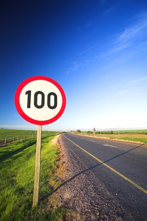Warning sign or road sign for the maximum speed limit next to an empty road on a sunny summer day. Focus on the numbers – saturated colors (polarized image)