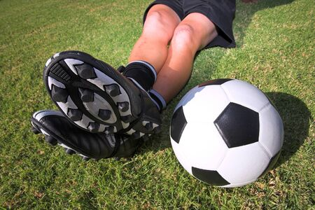 togs: A male soccer (football) player, referee or coach sitting with crossed legs. Focus on ball and togs