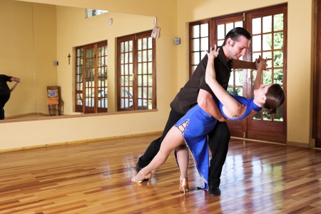 A young adult couple dancing and practicing ballroom dancing together in a studio - Focus on woman