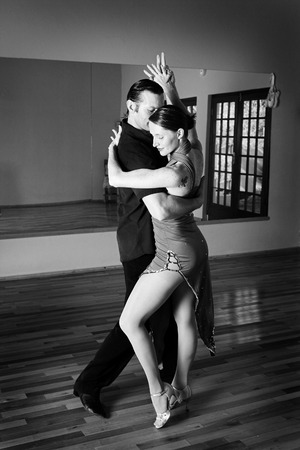 salsa dancing: A young adult couple dancing and practicing ballroom dancing together in a studio - Focus on woman, Black and white - high key efect