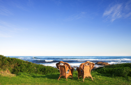 Wicker cane chairs on a lawn next to the sea Stock Photo
