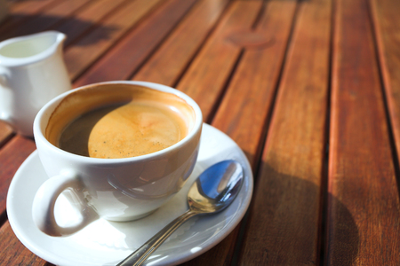 A cup of coffee on a wooden table in an outdoor cafe. Shallow depth of field, focus on the rim of the cup   photo