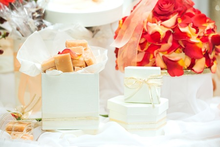 favour: Caramel fudge confectionery and white gift boxes with ribbons as wedding guest gifts and table decorations