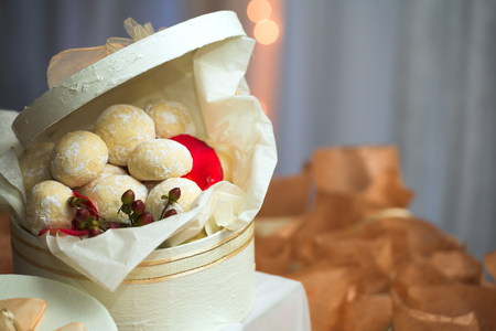 favour: Confectionery and cookies in white gift boxes with ribbons as wedding guest gifts and table decorations