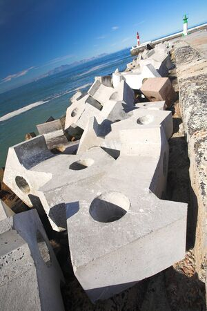 Big cement blocks (doloses) for storm water break outside the harbour wall, Kalkbay, Western Cape, South Africa � wide-angle perspective image Stock Photo - 1525573