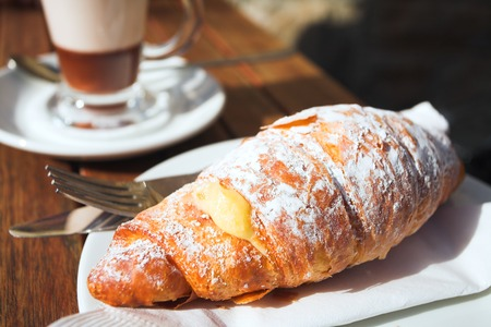 A cup of coffee and fresh cream croissant on a wooden table in an outdoor cafe. Very shallow depth of field, focus on top of croissant Stock Photo - 1525557