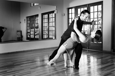 A young adult couple dancing and practicing ballroom dancing together in a studio - Focus on woman - Black and white, high key effect Stock Photo