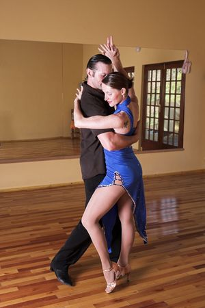 ballroom dance: A young adult couple dancing and practicing ballroom dancing together in a studio - Focus on woman