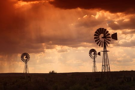 Brewing thunderstorm in the dessert area of the Karoo in South Africa just before sunset. Three wind pumps silhouetted against the skyline with sunbeams shining through the clouds.