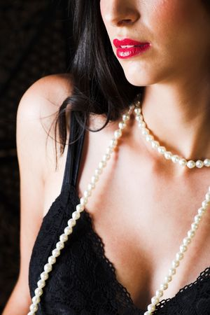 Sexy young Italian woman with red lips, black lingerie and a string of pearls Stock Photo