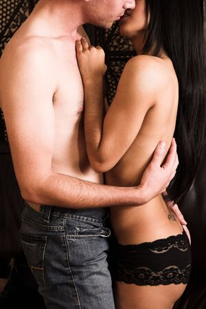 Multi-ethnic couple in passionate embrace and undressing each other in ually active foreplay