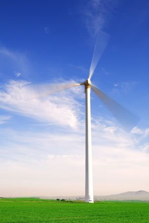 electricity generator: Wind powered electricity generator standing against the blue sky in a green field on the wind farm. (movement on blades) Stock Photo