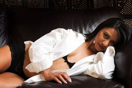 Sexy adult Indian woman in black lace lingerie lying on a brown leather couch with a white long sleeve shirt over her shoulders. Stock Photo - 2206187