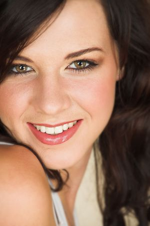 Young adult brunette woman with a white top and long brown curly hair and brown eyes looking at the camera and smiling