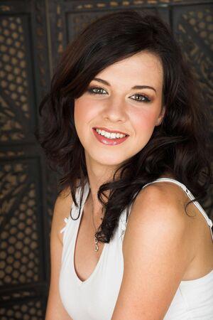 ojos marrones: J�venes adultos mujer morena con un top blanco y largo cabello casta�o rizado y ojos marrones mirando a la c�mara y sonriendo