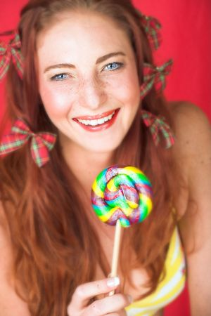 Young female adult fashion model with natural red hair and freckles in a yellow bikini with a big multi-colored lollipop (textured red faux leather background) - Very Shallow Depth of Field photo