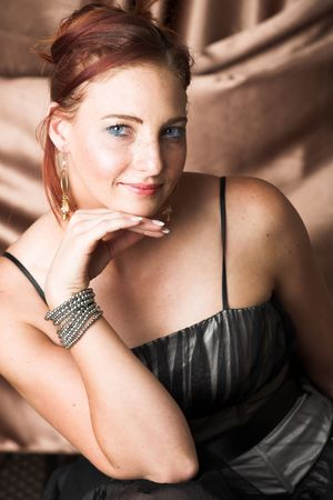 'evening wear': Young female adult fashion model with natural red hair and freckles in black chiffon evening wear with silver bracelet (Copper silk background) – hard light, high key image