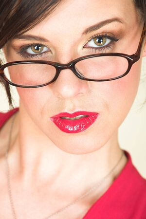 discreet: Young Caucasian adult businesswoman in a red, discreet, office wear with glasses, brown eyes, and red lips
